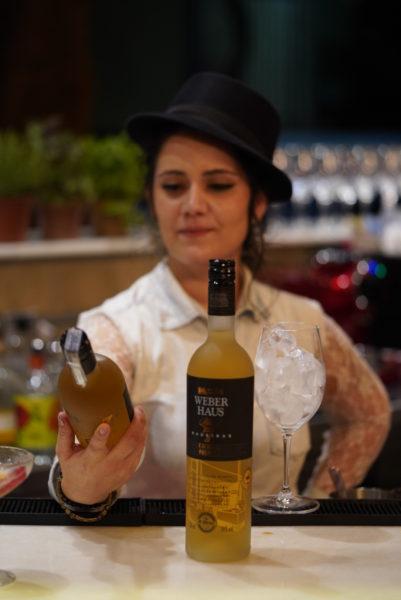 Bartender Jocassia Coelho contemplando uma garrafa de Weber Haus 7 Madeiras, Capitão Leitão, Belo Horizonte